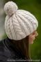 Вязаная шапка с косами и с помпоном